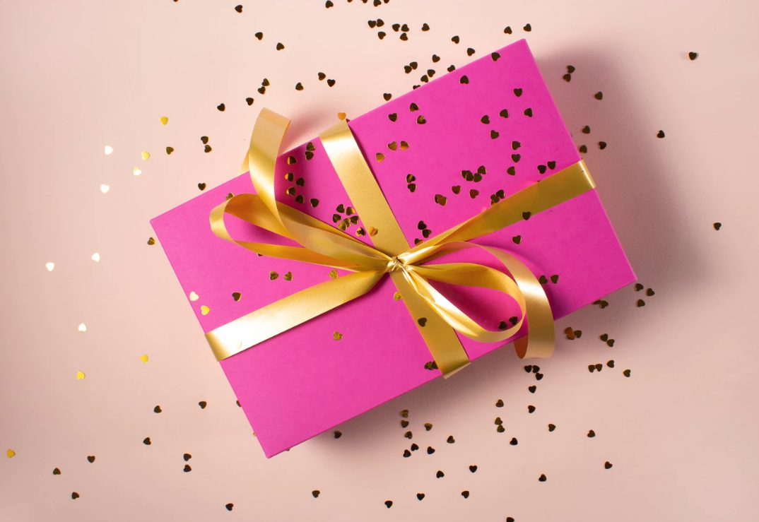 Present with pink paper and tied with a gold bow with glitter sprinkled over.