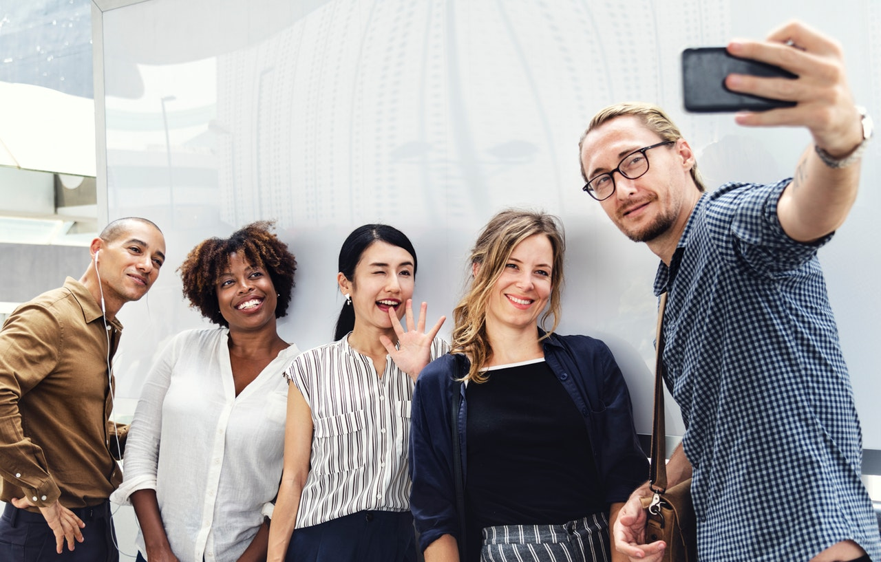 Group of five people taking a selfie in front of a white wall.