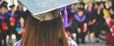 View of graduate's head from the back. They are wearing cap and gown, and other graduates similarly dressed in the background.